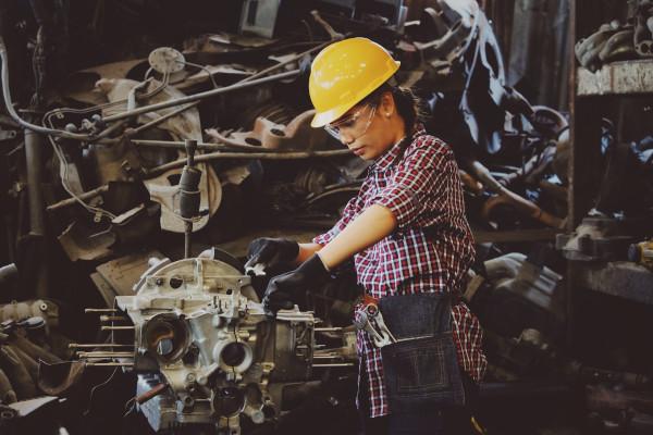 Frau in der mittelständischen Industrie bedient eine Maschine